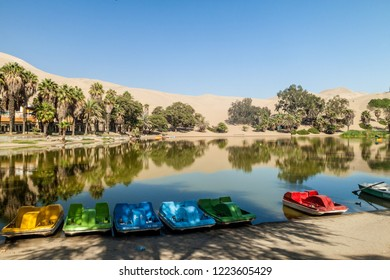 Small boats in desert oasis Huacachina near Ica, Peru