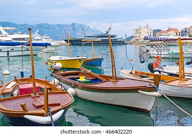 The small boats for hire are moored in port, next to the central city promenade, Budva, Montenegro.