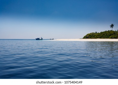 small boats landing on beautiful white sandy beach of deserted tropical island