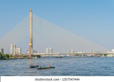 Small boats on the river Chao Phraya close to the Bhumibol Bridge in Bangkok, Thailand.