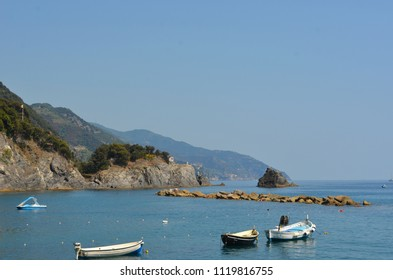 Small boats with outboard motors are moored in a quiet bay. A breakwater and a small island are in front of them, and rocky hills to one side. The sky is clear.