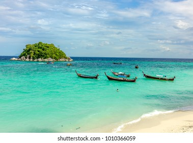A small boats and tropical island with blur view of its trees and boats from afar under blue sky of Lipe Island, Satoon province, Thailand