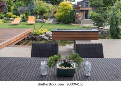 A small bonsai sits on a contemporary backyard patio table between two sculptured candles with a beautifully landscaped yard in the background.