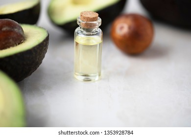 Small bottle of avocado oil and avocados on marble surface