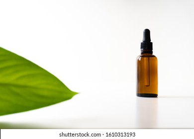 A small bottle with a dropper full of CBD oil or any other oil and a green leaf on white background