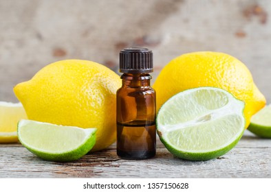 Small bottle of essential citrus (lemon and lime) oil on the old wooden background. Aromatherapy, spa and herbal medicine ingredients. Copy space.
