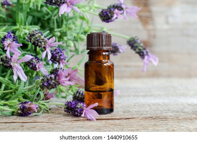 Small bottle with essential lavender oil. Lavandula flowers close up. Aromatherapy, spa and herbal medicine ingredients. Old wooden background. Copy space.