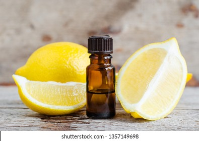 Small bottle of essential lemon oil on the old wooden background. Aromatherapy, spa and herbal medicine ingredients. Copy space.