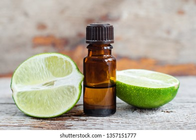 Small bottle of essential lime oil on the old wooden background. Aromatherapy, spa and herbal medicine ingredients. Copy space.