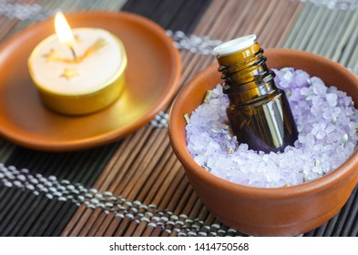 Small bottle of essential oil in the bowl with aroma bath salt and burning candle. Aromatherapy, spa and herbal medicine concept. Close up, copy space.