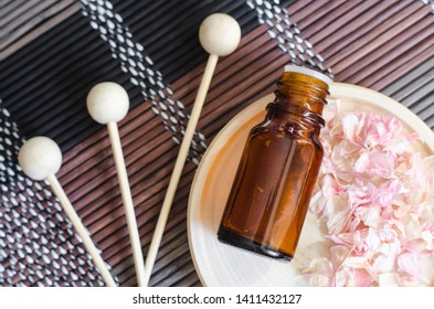 Small bottle with essential oil on the small plate, dry pink geranium flowers and wooden reeds. Background with dried flowers petals. Aromatherapy, spa, herbal medicine concept. Copy space, top view