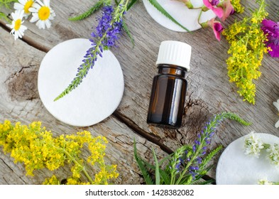 Small bottle with essential oil (tincture, infusion) and cotton pad. Aromatherapy and natural skin care concept. Old wooden background with field flowers. Top view, copy space.