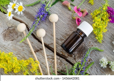 Small bottle with essential oil (tincture, infusion) and wooden reeds for aroma diffuser. Aromatherapy and natural skin care concept. Old wooden background with field flowers. Top view, copy space.