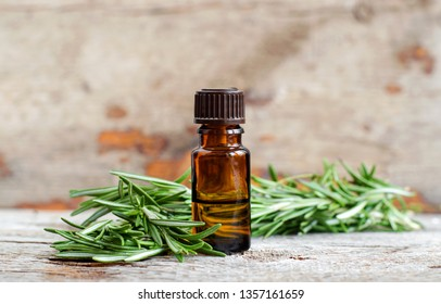 Small bottle of essential rosemary oil on the old wooden background. Aromatherapy, spa and herbal medicine ingredients. Copy space.