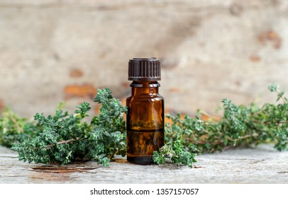 Small bottle of essential thyme oil on the old wooden background. Aromatherapy, spa and herbal medicine ingredients. Copy space.