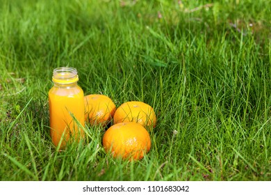 Small bottle of fresh orange juice in a park on a grass
