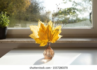 Small bouquet of autumn yellow leaves in sunlight. Still life, seasonal  decoration. Home decor,  ikebana style, Simple Leaf Arrangement.