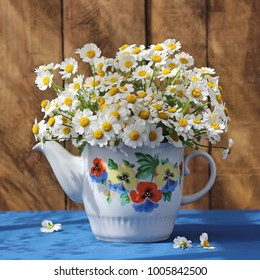 Small bouquet of daisies in a vintage teapot. Summer still life in rustic style.
