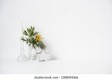 Small bouquet with green leaves and mimosa flowers and empty white wall