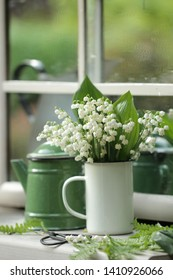 A small bouquet of lilies of the valley in a white enamel mug and a green enamel coffee pot on the window in the garden