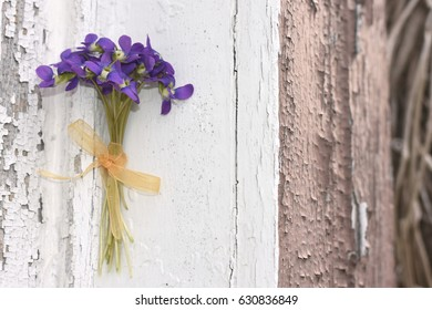 Small bouquet of violets on an old windowsill