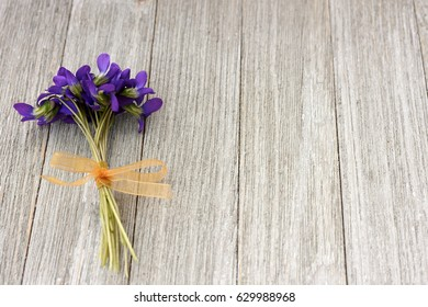 Small bouquet of violets on a wooden background