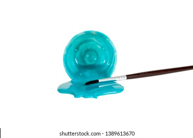 Small bowl of acrylic paint laying on its side with a small artist paint brush isolated on white