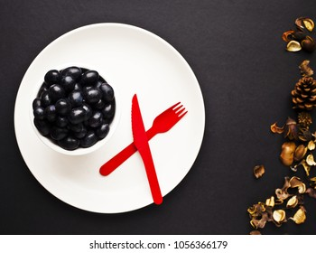 A small bowl of black grapes on plate, with red knife and folk on black surface