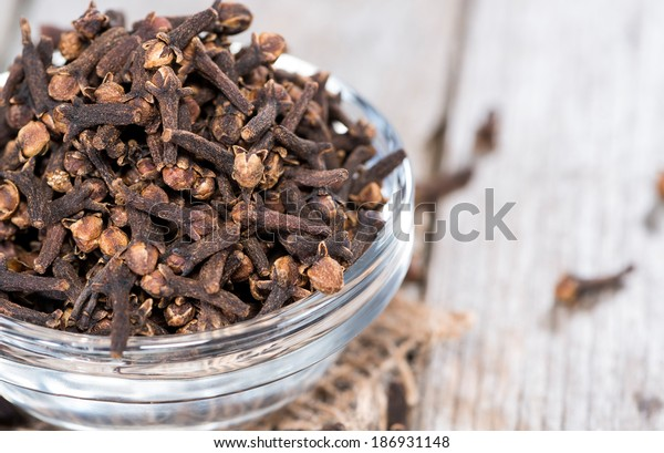 Small bowl with Cloves on vintage wooden background