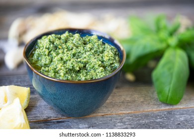 Small bowl of fresh pesto on wooden table with pesto ingredients