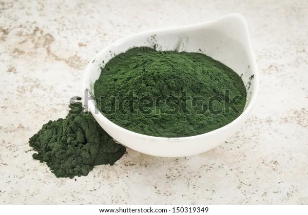 small bowl of Hawaiian spirulina powder against a ceramic tile  background