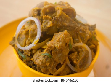 A Small Bowl of Nkwobi, A tasty Nigerian Outdoor Delicacy made with Soft Cow Meat and Spicy Oil Sauce. Garnished with Onions and Green Spices