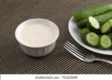 A small bowl of ranch dressing with sliced and whole bite size cucumbers on a white plate plus a fork in the foreground on a tablecloth.