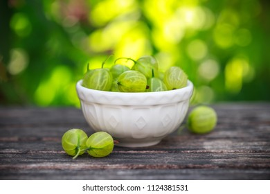 small bowl of Ripe gooseberries on a wooden table in the summer garden