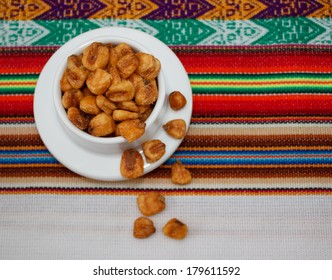 Small bowl of toasted salted corn seeds on peruvian tablecloth