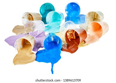 Small bowls of assorted colors acrylic paint laying on its side isolated on white