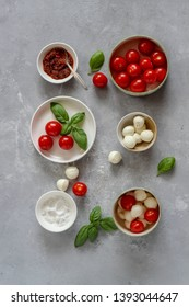 Small bowls with colorful ingredients of Caprese salad on a dark background, flat lay style