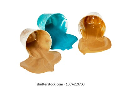 Small bowls of spilled tan and aqua blue acrylic paint laying on its side isolated on white