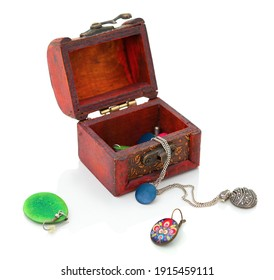 Small box for children with children's earrings and chains. Children's jewelry isolated on white background with shadow reflection.