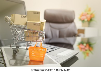 Small boxes in a shopping cart and an orange plastic shopping basket on a smart tablet and a laptop. Concept of online / virtual shopping that will replace the old style shopping in the next few years