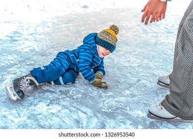 A small boy 3-4 years old, fell on the ice in the winter ice skating. Mom raises her son. Happy smiles. Learning skating support the first fall.