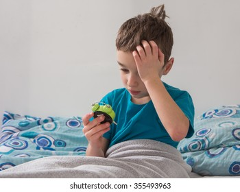 The small boy  with alarm clock in  the bed , wake up