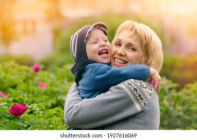 A small boy in the arms of a middle-aged woman is hugging and laughing.