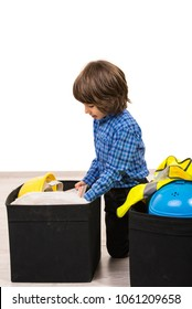 Small boy arrange construction tools in boxes against white background