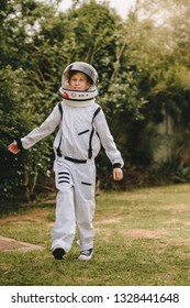 Small boy in an astronaut suit playing outside. Kid pretending to be an astronaut.