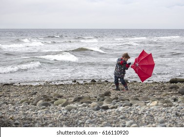 Small boy at the beach holding an umbrella that has turned inside out in the strong wind.