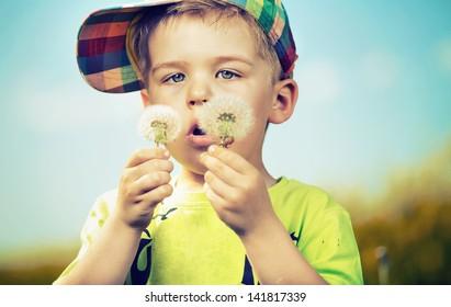 Small boy blowing dandelions