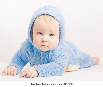 Small boy in blue overalls on white background