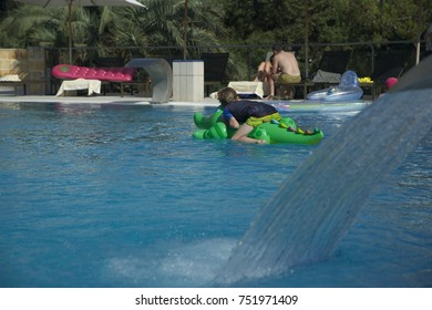 Small boy in a calypso playing with inflatable crocodile in outdoor swimming pool, Summer, people on the background