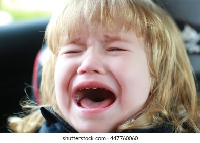 small boy child with facial emotions on unhappy crying face and long blonde hair sitting in car with tear on cheek, closeup